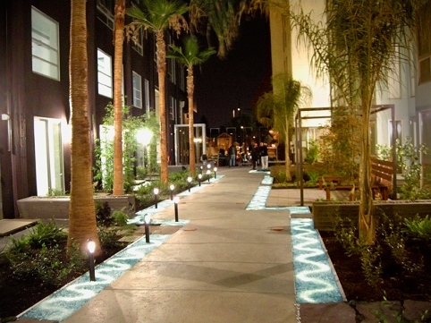 The Dining Room Court at night. Rainwater harvesting includes infiltration 'rivers' of crushed glass, uplit with LED lighting.